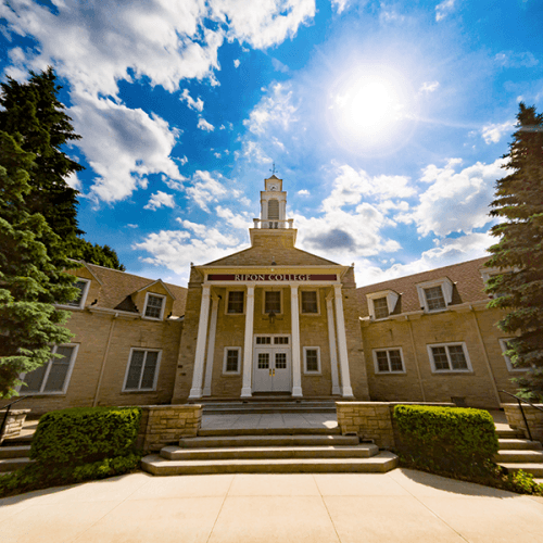 Photo of Harwood Memorial Union with clouds and sun