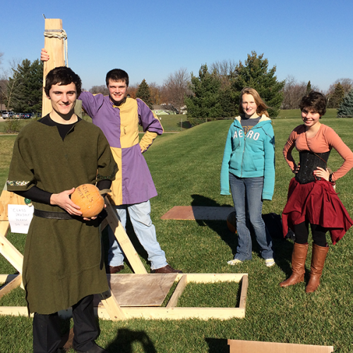 Photo of students in medieval garb preparing pumpkins for launching