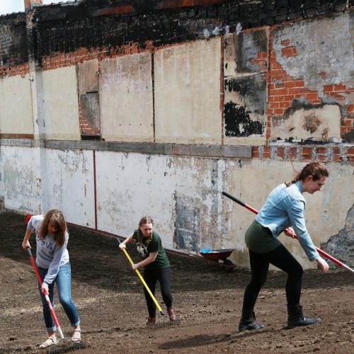 Photo of three female students raking ground