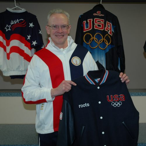 Photo of Kent Timm holding an Olympic jacket