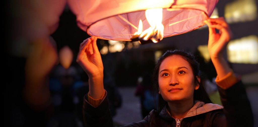 young woman letting a flaming lantern go into the sky