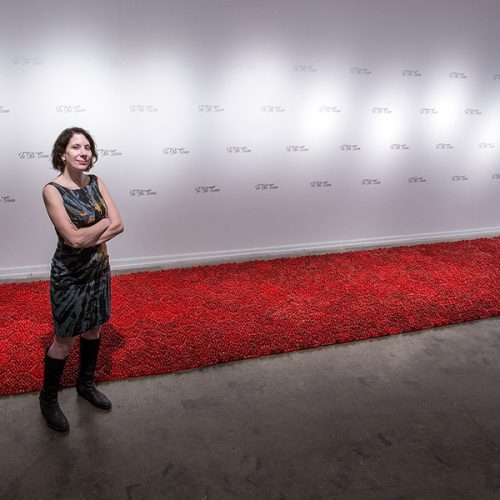 Artist Sarah Gross standing before some of her work